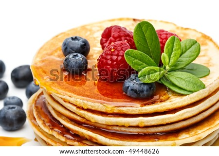 Small pancakes topped with honey, raspberries and bilberries on white background
