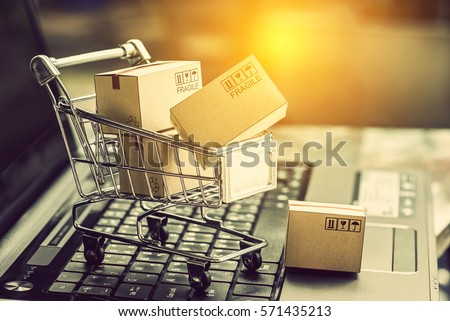 68ff70106f3 Small paper cartons or boxes in shopping cart with one falls outside on a laptop  keyboard