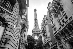 Small paris street with view on the famous Eiffel tower on a cloudy rainy day in black and white