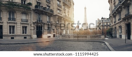 small paris street with view on the famous eiffel tower on a cloudy rainy day with some sunshine