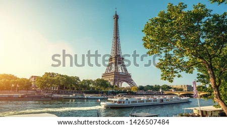 Photo of small paris street with view on the famous paris eifel tower on a cloudy rainy day with some sunshine