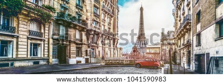 Photo of small paris street with view on the famous paris eiffel tower on a cloudy rainy day with some sunshine - wide horizontal panorama