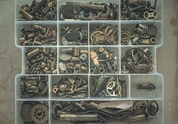 Small parts made of brass, copper, iron.Gears, tubes, wire, bolts, cogs in the case for small things.Technical background.