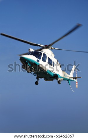 Small passenger helicopter hovering on blue sky.