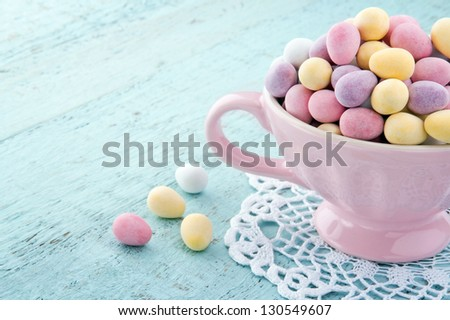 Small pastel color easter eggs in a pink cup on light blue wooden table, with copy space