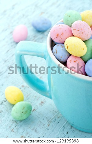 Small pastel easter eggs in a light blue cup on vintage wooden background