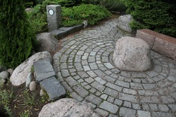 Small path with stone in front of  narrow pathway in a park.