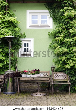 Small patio or street garden with rustic chair and table and plants climbing on a green house wall.