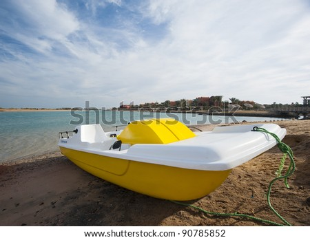 Small pedal boat on a tropical beach with an overcast sky background