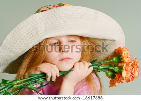 Small pensive girl in a big hat with pink flowers