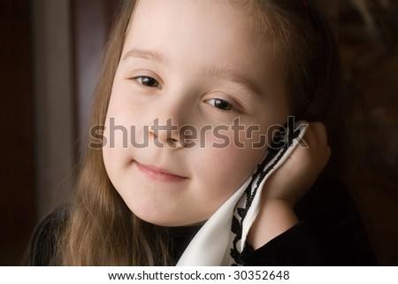 Small pensive girl on dark background. Portrait