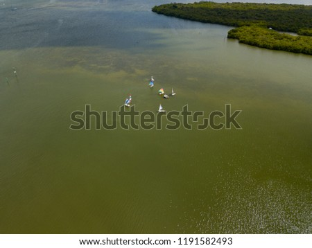 Small personal sailboats in a shallow inland waterway in Florida seen from an aerial drone image