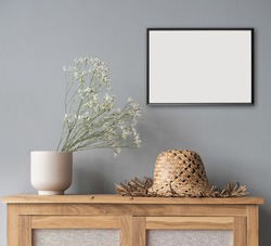 Small picture frame mockup on gray wall. Artwork in modern interior design. Empty white copy space for artwork showcase.