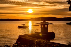 Small pier with a tiny house in a fantastic sunset. Sailboat anchored in the bay