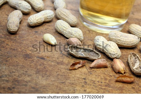 Small pile of peanuts in shells with draft beer over wood background