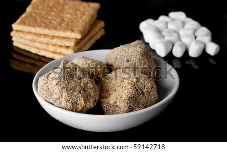 small pile of smores truffles in a bowl over a black background