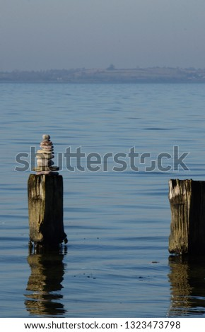 Small pile of stones balancing on a wood log standing in the sea Stock foto ©