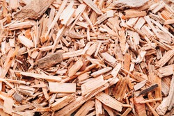 Small pile of wood chips background, top view. Waste from the woodworking industry, fuel and raw materials for heating solid fuel industrial boilers on wood chips