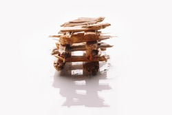Small pile of wood chips in view of log cabin fire constructed by criss crossing wood in opposite directions of each other on white background. Biofuel concept with  hieroglyph reflection