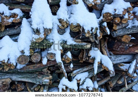 Small pine gray firewood in a heap under white snow on the street #1077278741