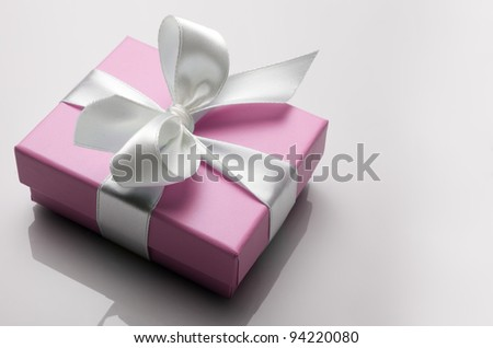 small pink box tied with a white ribbon