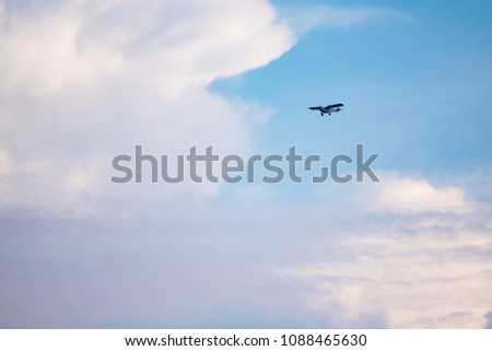 Small plane in the air. Blue sky with white clouds #1088465630