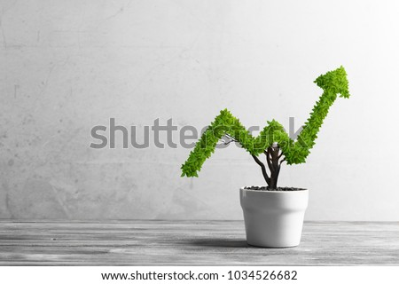 Small plant in pot shaped like growing graph #1034526682