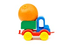 Small plastic colorful toy truck with one big mandarin fruit in basket on white background