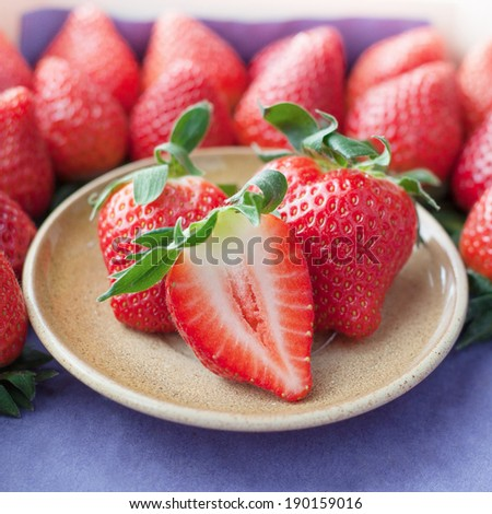 Small plate filled with succulent juicy fresh ripe red strawberries on table