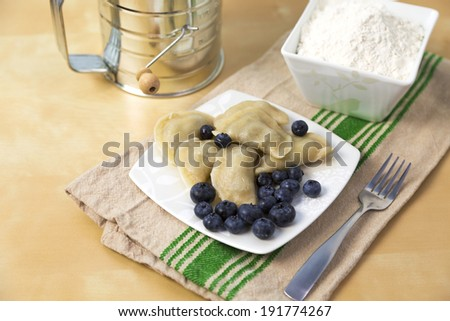 small plate full of Polish pierogi with blueberry filling