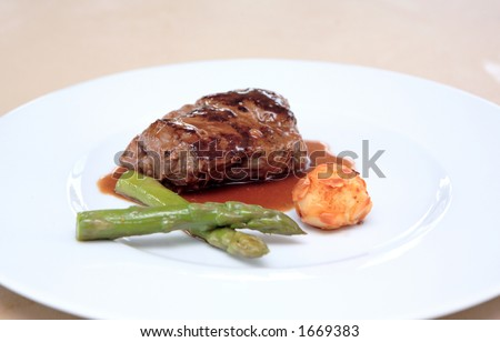 Small plate of gourmet food including fillet of steak meat, asparagus and potato