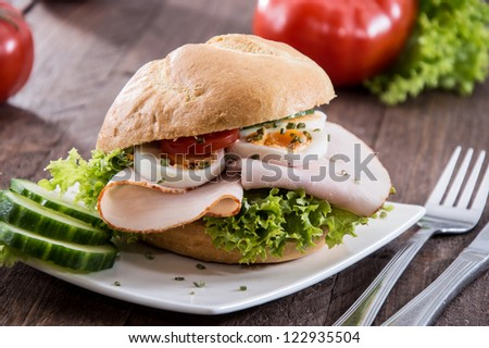Small plate with Chicken Sandwich on wooden background