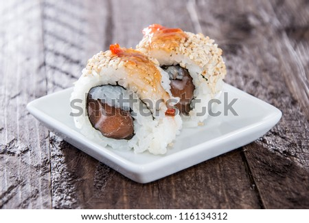 Small plate with Sushi Rolls on wooden background