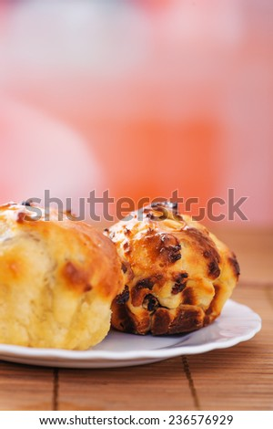 Small plates of muffins on ppink background.
