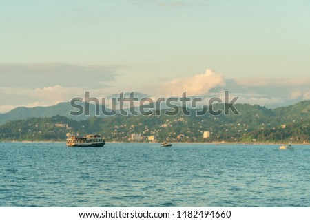 Small pleasure tourist boat floating from the port for a cruise off the coast on a Sunny summer evening against the background of the mountains, Batumi