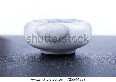 Small polished black and white marble bowl on a black background