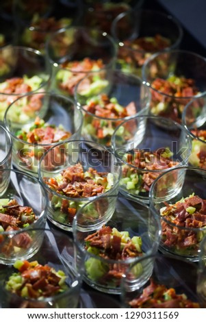 Small portions of salad with meat and avocado slices.