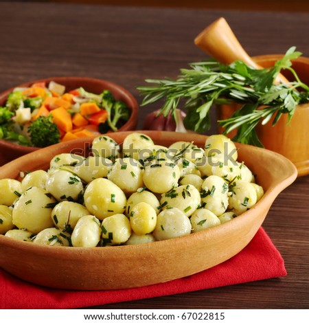 Small potatoes with herbs, such as parsley, thyme and rosemary with fried vegetables and a mortar with herbs in the background (Selective Focus, Focus on the front of the potatoes and the bowl)