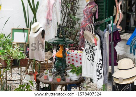 small private cozy eco shop or store selling clothes and various things on the street, things are hung on a hanger #1578407524