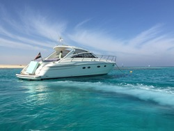 Small private yacht in the sea with beautiful turquoise wave and lightly stretched clouds