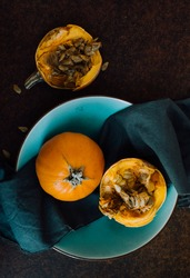 Small pumpkins placed in a bowl on dark background. Studio still life.