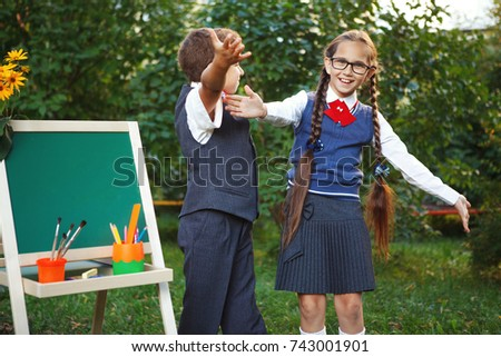 Small pupils a boy and a girl at the blackboard have fun laughing in the Park. copyspace #743001901