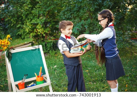 Small pupils a boy and a girl at the blackboard have fun laughing in the Park. copyspace #743001913