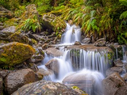 Small Rainforest waterfall long exposure image in lush tropical forest