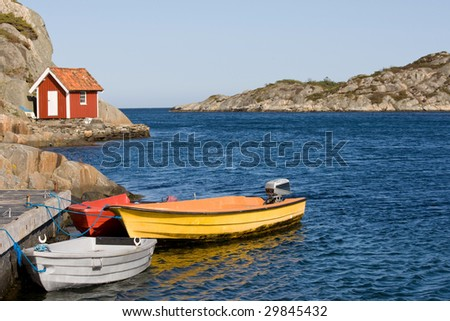 Small red and white hut by the sea in southern Norway. Some small colorful boats in the foreground.
