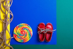Small red boat shoes near big multicolored lollipop and rope on colored background.  Top view. Copy space, frame