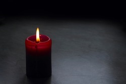 Small red candle with dark dark background. One candle on the table. Burning candle against the wall, mourning