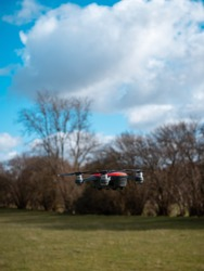 Small red drone flying low. Sky and trees background. Spinning propellers. Unmanned aircraft system. UAV