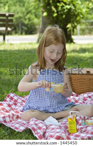 Small red-haired girl eating a cup of applesauce outdoors in a park - picnic setting.