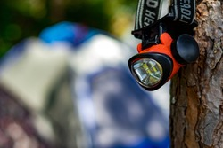 small red head lamp for camping hanging on the tree with unfocused camping tent. travel and camp theme